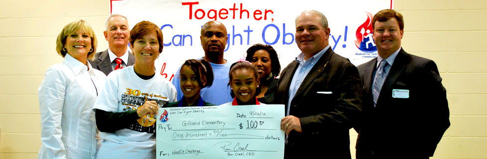 State Representative Jim Barton helps ASF Foundation present the check to Gilliard Elementary Physical Education Department.